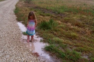 Young girl in puddle on farm